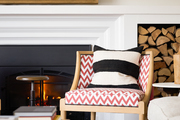 Patterned chair and striped throw pillow in front of a fireplace.