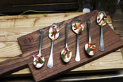 Small Hors d'oeuvres atop wooden serving tray.