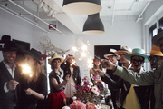 Guests hold sparklers over a flower topped table