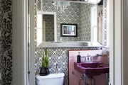 Black and wallpaper contrasts pink tile in the powder room