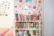 A bookshelf against floral-patterned wallpaper and a sisal rug