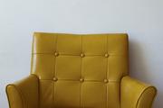 A classic upholstered armchair with a tufted back