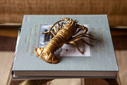 A brass lobster objet on a glass-topped cocktail table