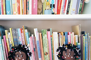 Books and a pair of dolls on white shelves