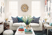 A white couch, coffee table, and pouf atop a blue patterned rug