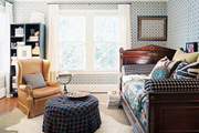 A leather wingback chair and a wooden daybed in a patterned-filled guest room