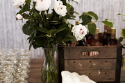 Flowers and bar necessities atop wooden table.