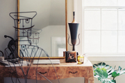 An iron chair paired with a wooden desk and a gold-frame mirror