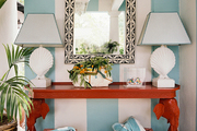Striped walls with a pair of clamshell lamps on a red elephant-motif console