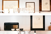 Dishes and framed drawings on open shelving in a kitchen