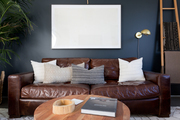 A contemporary living space with navy blue walls and a brown leather couch.