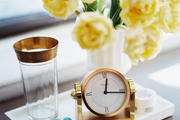 A gold clock and a vase of yellow peonies on a white tray