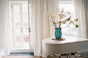 A wall of white curtains with a white piano atop a natural-fiber rug