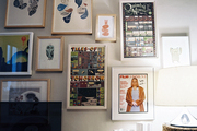 A grouping of art above shelves holding a record player and a cork-edged lamp