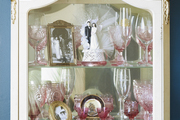 Pink glassware is displayed in an ornate glass cabinet.