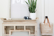 A wooden console table in an entryway.