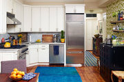 White cabinetry and a blue rug in an open kitchen
