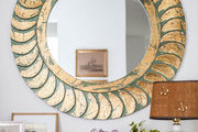 A round gold mirror above a console table