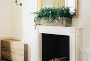 A white mantel topped with a rectangular mirror and a planter