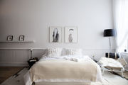 A bedroom done in white; framed artworks on the wall