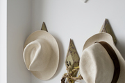 A detail of hats hanging on a wall.