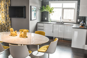 Contemporary gray, white, and yellow dining area in a kitchen.