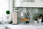 A marble kitchen counter with a mossy green tile backsplash