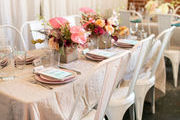 A neutral tablescape with pink plates and pink flowers.