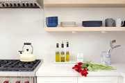 Floating wood shelves and white countertops in a kitchen