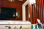 Striped walls and a sconce in a bathroom with white countertops