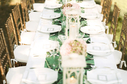 An elegant outdoor dinner table set with gold chairs