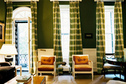 Green striped curtains behind a pair of chairs and a brass floor lamp