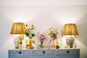 Ceramic lamps and vases of flowers on a wooden sideboard