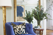 A brass floor lamp and gold-leaf mirror paired with a violet tufted chair