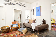 A comfortable living area with a bold wall art and patterned rugs.