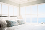 White bedding and blue patterned pillows in a bedroom with views of the ocean