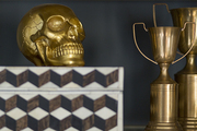 A vignette consisting of a marquetry box, brass trophies, and a golden skull