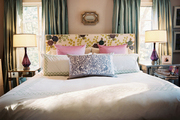 Green curtains and an upholstered floral headboard with white bedding