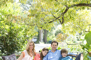 Designer Tami Ramsay and family on a rattan sofa in an outdoor seating area