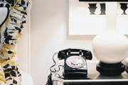 A white lamp and a telephone on a mirrored bedside table