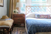 White, blue, and brown bedroom with Chippendale headboard.