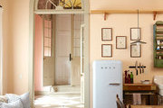 A vintage-style kitchen in New Orleans leads to a bold pink entryway