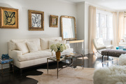 A contemporary living room with a white sofa and paintings in gold frames.
