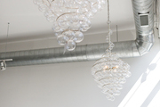 A pair of bubble chandeliers next to industrial duct pipes
