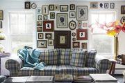 Art covered walls atop a plaid patterned couch.