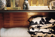 Black-and-white floral pillows and a light-gray throw on a wooden shelf