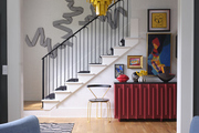 eclectic staircase and entry with red credenza, yellow chandelier and vintage accent furniture