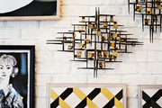 Geometric art pieces hung on a white brick wall
