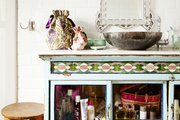 A vintage cabinet in a bathroom with white subway tile