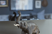 An elephant atop a drum in a living room corner